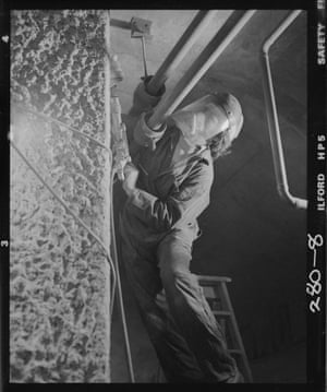A construction worker hand-drills the textured effect on the concrete walls (Nov 1979)