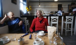 Mark Cox and Nell Nelson, sitting at a table in a cafe, smiling and laughing
