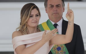 Brazil's new first lady Michelle Bolsonaro communicates with sign language, as her husband President Jair Bolsonaro stands by, at the Planalto Presidential palace, in Brasilia, Brazil, Tuesday, Jan. 1, 2019. (AP Photo/Silvia Izquierdo)