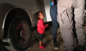 A two-year-old Honduran asylum seeker cries as her mother is searched and detained near the US-Mexico border, in McAllen, Texas