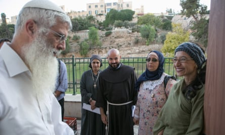 A member of the congregation is welcomed at the entrance of Amen by, right to left, Rabba Tamar Elad-Abblebaum, Waida Ibtisam Mahmeed, Father Alberto Fer and Sister Esther Salib