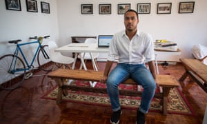 Rashiq Fataar, founder and director of Future Cape Town, an independent non-profit organisation, sits at a table in a white studio space.