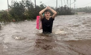 Matthew Aylen wades through waist deep water as he is rescued from her flooded home during Hurricane Dorian in Freeport, Bahamas, Tuesday, Sept. 3, 2019. Practically parking over the Bahamas for a day and a half, Dorian pounded away at the islands Tuesday in a watery onslaught that devastated thousands of homes, trapped people in attics and crippled hospitals.