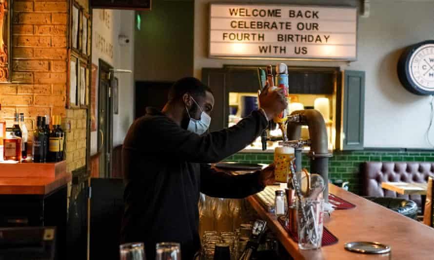 A bartender pours a pint of beer at a pub in London