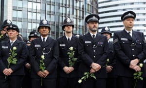 Police officers hold flowers on Westminster Bridge
