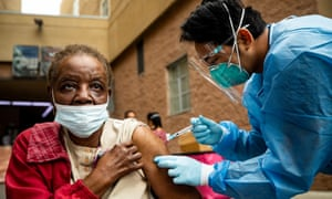An 86-year-old woman is vaccinated against Covid-19 as part of a vaccination drive for homeless people in Los Angeles.