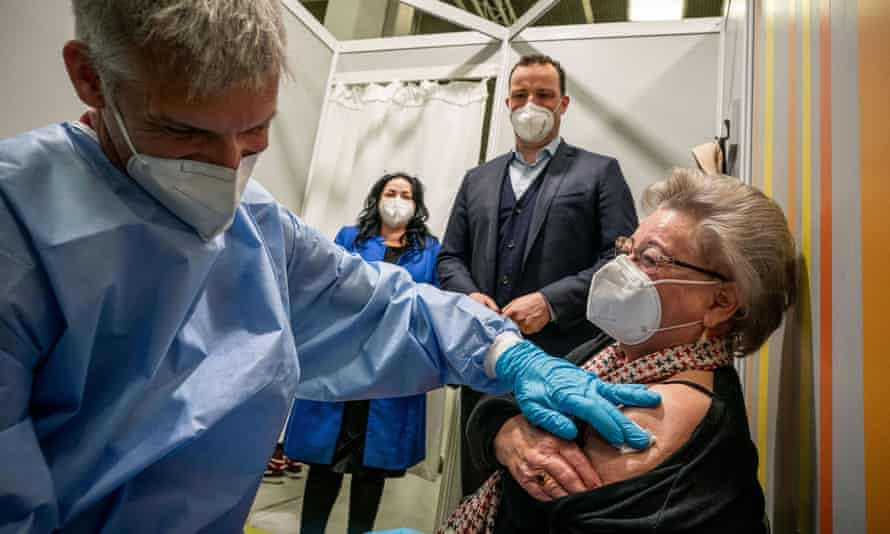 The German health minister, Jens Spahn, visits a vaccination centre in Berlin as a woman receives a second dose of the Pfizer/BioNTech coronavirus vaccine on Monday.