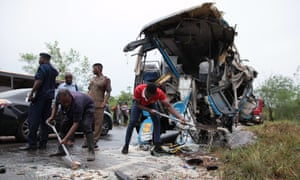 Fire service personnel clean up debris at the scene of a bus crash in Kintampo, Ghana