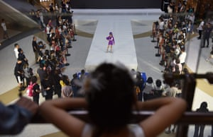 A young girl watches a competitor on the catwalk