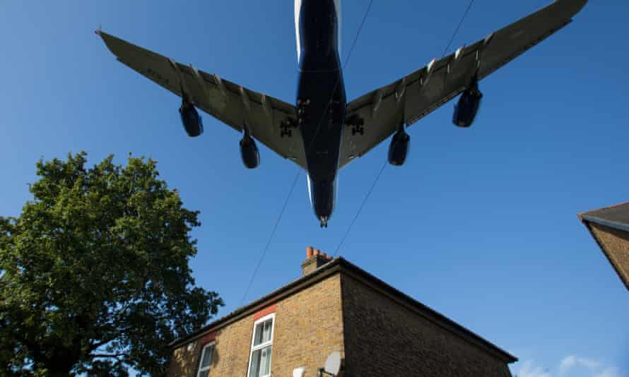 A plane flying over a house in west London