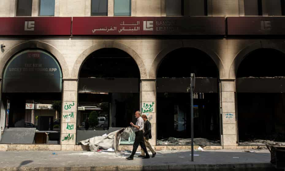 Pedestrians walk past a bank that was attacked and burned by demonstrators in Tripoli.