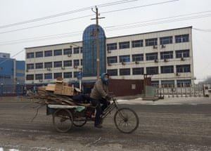 A man cycles past the abandoned Fufeng steel offices.