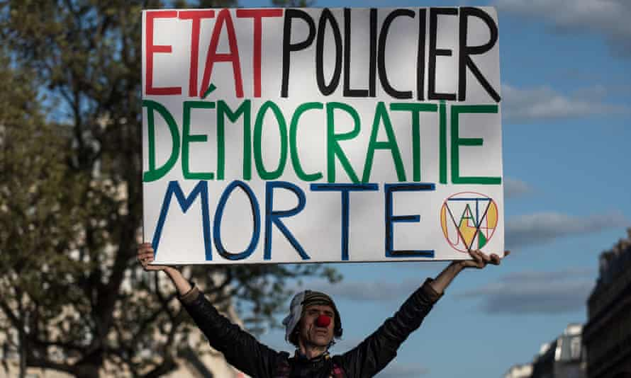 """Deliver your message ... activist poet Jean-Baptiste Redde, aka Voltuan, holds a placard reading """"police state is the death of democracy"""" as people gather on the Place de la Republique in Paris on May 3 to protest against the government's labour reform bill."""