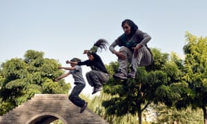 Iranian women practice parkour skills at a park in Tehran.
