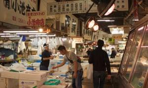 Customers examine the fare at Tsukiji market in Tokyo.