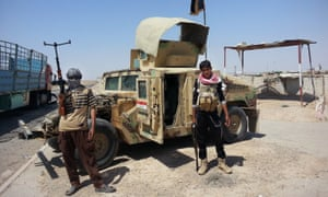 Islamic State militants with a captured Iraqi army vehicle at a checkpoint outside Baji refinery in Iraq.