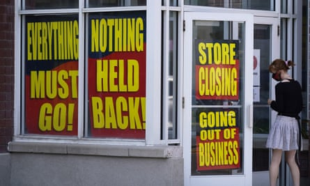 Store closing signs line a window of a business in Salt Lake City.