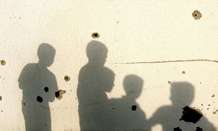 The shadows of palestinian children cast on a bullet riddled wall of a destroyed house in the northern Gaza Strip