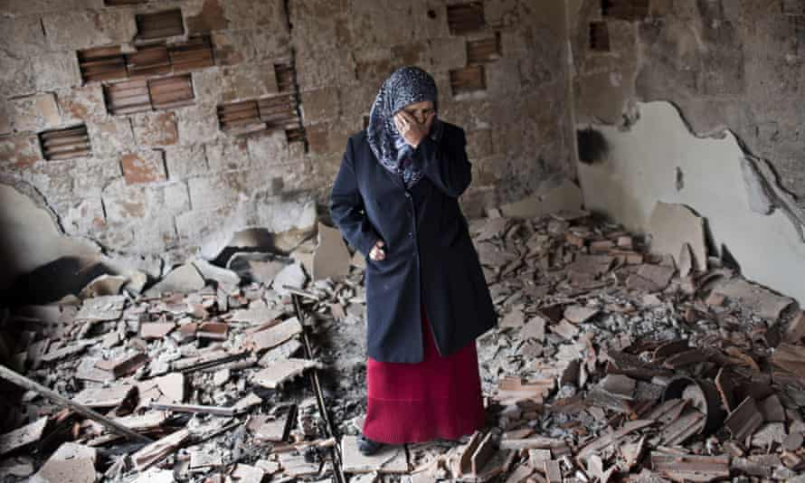 Habibe Biyali stands inside a room in her house heavily damaged by fighting in Kumanovo, Macedonia.