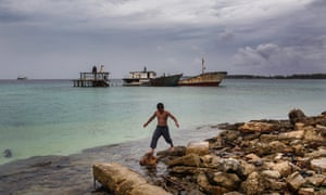 A child plays near abandoned ships on Majuro, the capital of the Marshall Islands.