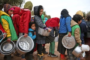Children queue to receive food distributed by humanitarian aid workers near the village of Yazi Bagh in Syria.