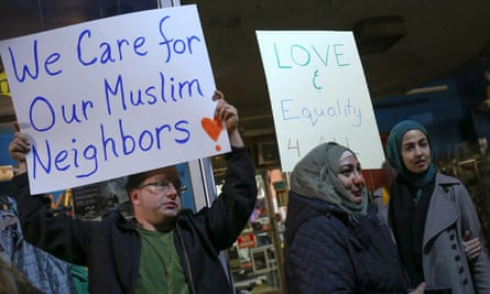 Protesters hold signs during demonstration against President-elect Trump and in support of Muslim residents in Hamtramck, Michigan.