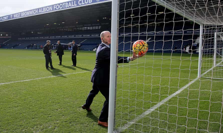 The referee Mike Dean tests goalline technology before a match
