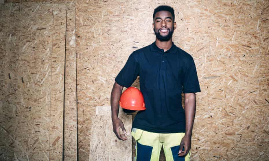 """Portrait of confident carpentry student holding hardhat while standing against wooden wall"""""""""""