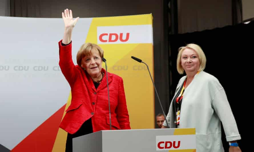 Angela Merkel waves as she arrives at an election rally in Wismar with Karin Strenz.