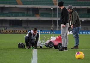 Groundsman make some last-minute adjustments at the Stadio Marcantonio Bentegodi.
