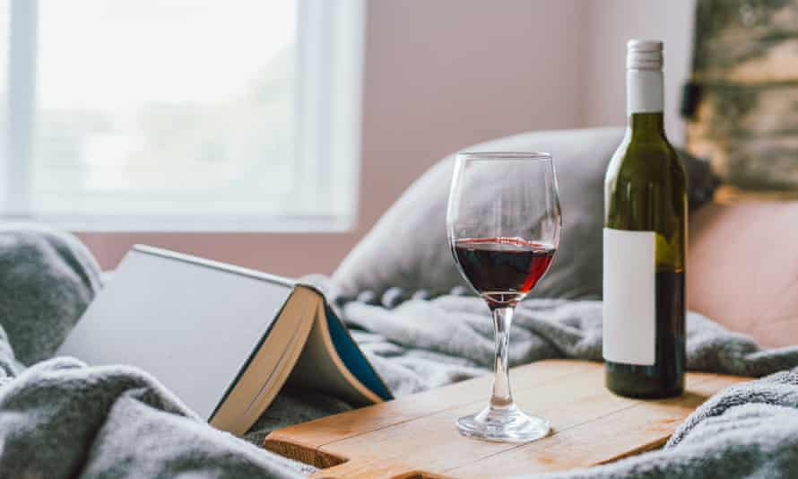A single glass of red wine, and half empty bottle and a book on a bed in a home