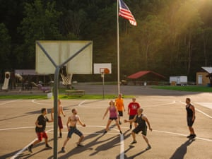Young people play basketball on a summer afternoon in Webster Springs, West Virginia on 23 July 2018. A photographer and poet collaborated to create a series of photographs and poems of this often-stereotyped region of America. While most narratives emerging from West Virginia deal with opioids, coal, or politics, the words and images compiled speak to a deep connection between individuals, their community, and the geographically complex location that gives birth to West Virginian culture.