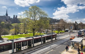 Trams run along Princes Street in Edinburgh.