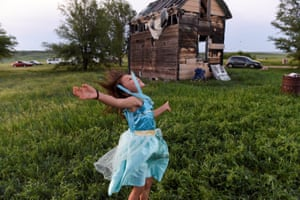 One of Beatrice Lookinghorse's granddaughters, Rozelynn Whitebull, plays near an abandoned house in the backyard of Beatrice Lookinghorse's trailer on the Cheyenne River Reservation in Green Grass, South Dakota.