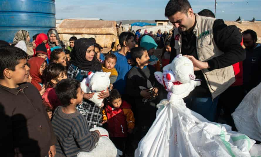 Children wait in queue to receive toys supplied by Humanitarian Relief Foundation.