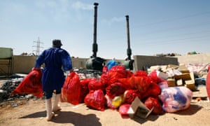 Workers wearing protective suits in Iraq collect garbage from hospitals of patients infected with coronavirus