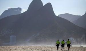 Police officers patrol the closed Ipanema beach in Rio de Janeiro