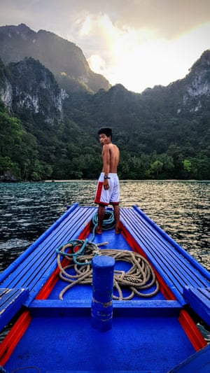 By Sophie Titmus. Arriving at an uninhabited island on the last night of a Tao boat expedition in the Philippines' Palawan archipelago. The skipper, pictured, was about to weigh anchor for the final time, as mist rolled over the mountains and the sun was setting.