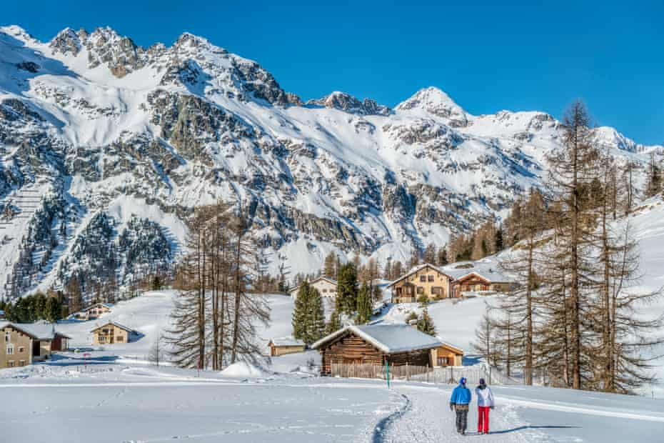 Walking couple in winter landscape in Val Fex in Engadine, Grisons, Switzerland.