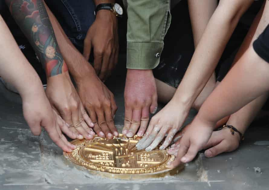 Pro-democracy protesters install a plaque declaring 'This country belongs to the people' at Sanam Luang in Bangkok