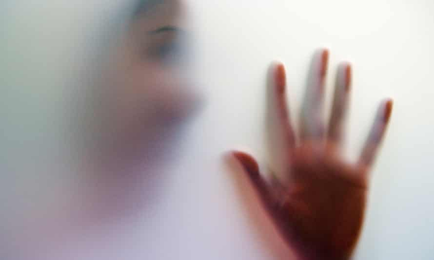 Shadowy figure of a young woman with face and hand held up against a glass door