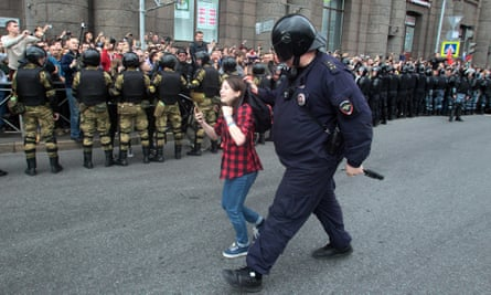 A Russian police officer detains a teenager during rally in St Petersburg protesting against retirement age increases.