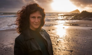 scientist camille parmesan standing on a beach in south-west england with the sun going down behind her