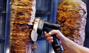 A man slices cuts of meat from a rotisserie doner spit inside a cafe in Frankfurt, Germany.