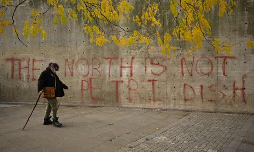 A woman wearing a face-mask walks past graffiti declaring that 'the north is not a petri dish' on 16 October.