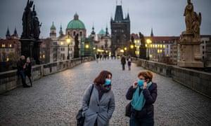 Women wearing face masks walk on Charles Bridge at dusk in Prague, Czech Republic