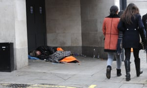 People walking past a rough sleeper