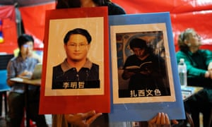 A volunteer holds placards of detained Taiwanese activist Lee Ming-cheh and Tibetan education advocate Tashi Wangchuk.