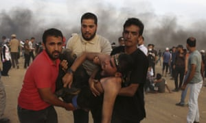 Protesters evacuate a wounded youth from near the fence of the Gaza Strip border.