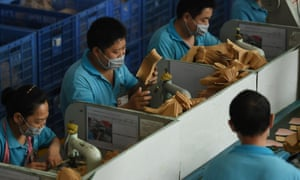 Workers staff a production line at a Huajian shoe factory in Dongguan, southern China.